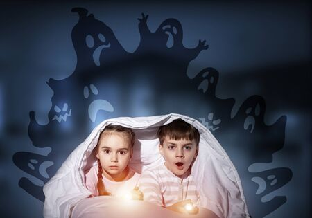 Scared children in pajamas with flashlights hiding under blanket. Frightened kids sitting in bed. Children and boo ghosts above them. Comic evil spirits silhouettes on background. Childhood fears.