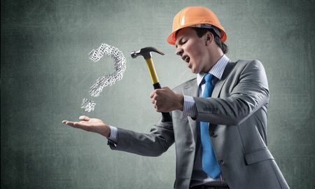 Furious businessman going to crash with hammer question mark. Young handsome man in business suit and safety helmet standing on wall background. Search for solution and realization. Risk management