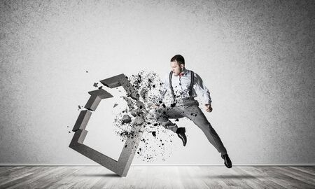 Determined businessman jumping and breaking with kick house concrete figure