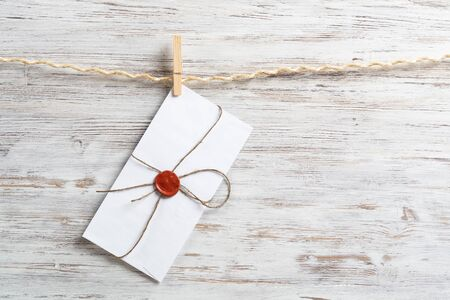 White envelope hanging on rope on wooden background. Twine rope with wooden clothespins. Letter envelope with wax seal stamp. Retro communication and correspondence. Delivery service layout