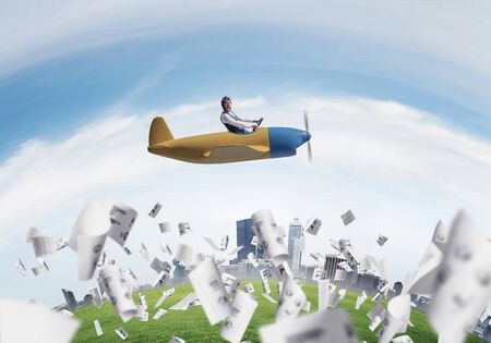 Emotional pilot in leather helmet and goggles sitting in propeller plane. Aviator driving airplane above falling paper sheets with infographics. Rounded city skyline with blue sky and high skyscrapers