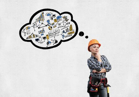 Concentrated female construction worker in safety helmet standing with folded arms. Pensive young technician with speech bubble above head on white background. Business idea generation concept Фото со стока