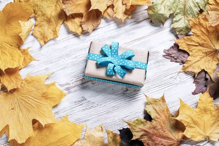 Flat lay autumn composition with gift box and yellow autumn leaves. Holiday present decorated blue ribbon bow on vintage wooden desk. Happy thanksgiving congratulation. Autumn sale advertising. Фото со стока