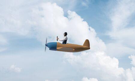 Jonge man in vliegeniershoed met bril die propellervliegtuig drijft. Reizen rond de wereld per vliegtuigconcept. Grappige mens die in klein vliegtuig in hemel met wolken vliegt. Extreme luchtvaarthobby.