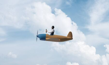 Young man in aviator hat with goggles driving propeller plane. Traveling around the world by airplane concept. Funny man flying in small airplane in sky with clouds. Extreme aviation hobby.