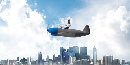 Business direction and motivation concept with pilot sitting in cabin of small airplane. Funny man in aviator hat and goggles driving propeller plane above city. Modern metropolis with high buildings