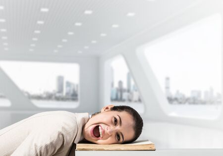 Bored business woman lying on desk with open book. Tired lady yawning in light office interior. Young female worker in white suit being sleepy head. Paperwork deadline and overwork in office concept.