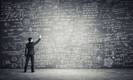 Businessman or teacher drawing science sketches at blackboard Imagens