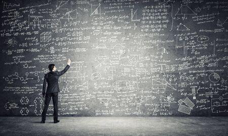 Zakenman of leraar die wetenschappelijke schetsen trekt op blackboard black Stockfoto