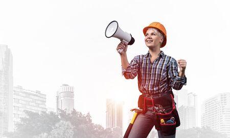 Attraktive Bauarbeiterin im Schutzhelm mit Megaphon. Porträt des jungen lächelnden Ingenieurs im karierten blauen Hemd auf nebeligem Hintergrund der Metropole. Ankündigung und Verkaufsförderung