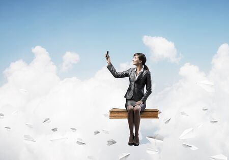 Attractive girl sitting on big book and flying in blue sky. Young woman in business suit using smartphone. Pretty businesswoman on background cloudscape panorama with paper planes.