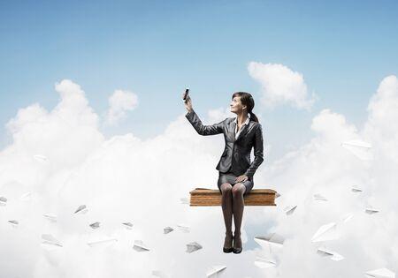 Muchacha atractiva que se sienta en el libro grande y que vuela en el cielo azul. Mujer joven en traje de negocios con smartphone. Bonita empresaria en el panorama del celaje de fondo con aviones de papel.