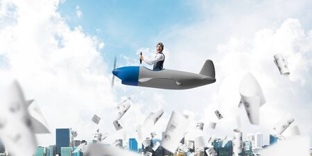Businessman in aviator hat and goggles driving propeller plane above cityscape. Papers falling down on background of blue sky with clouds. Expression pilot having fun in small airplane.