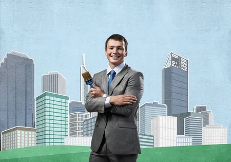 Confident and creative businessman painter standing with arms folded. Happy handsome man in business suit and tie holding paintbrush on background cityscape illustration. Creativity in business. Stock Photo