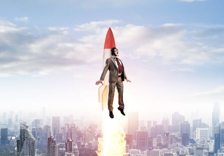 Businessman in suit and aviator hat flying on rocket. Superhero businessman flying with jetpack rocket in blue sky above modern downtown. Successful business startup. Career growth concept. Фото со стока
