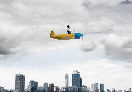 Businessman in aviator hat and goggles driving propeller plane above downtown with high buildings. Funny man having fun in small airplane. Modern megalopolis panorama with cloudy sky