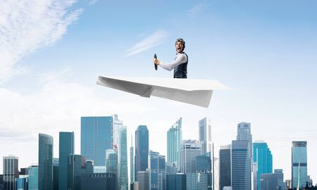 Scared pilot with open mouth sitting in paper plane and holding steering wheel. Aviator driving paper plane above business center in blue sky. Cityscape with high skyscrapers and office buildings.