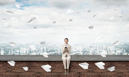 Beautiful young woman playing trumpet on roof. Brave girl in white business suit with music brass instrument sitting on edge of roof. Mixed media business concept. Flying paper planes in blue sky