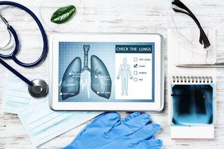 La diagnostica medica nella moderna pneumologia. Computer tablet con interfaccia dell'applicazione medica sullo schermo. Immagine a raggi x vista dall'alto, stetoscopio e cardiogramma sulla scrivania. Test di screening digitale della tubercolosi