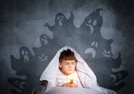 Frightened child with flashlight hiding under blanket. Scared kid with closed eyes lying in bed at home. Little boy in pajamas can not sleep at night. Halloween scary ghostly monsters on wall.