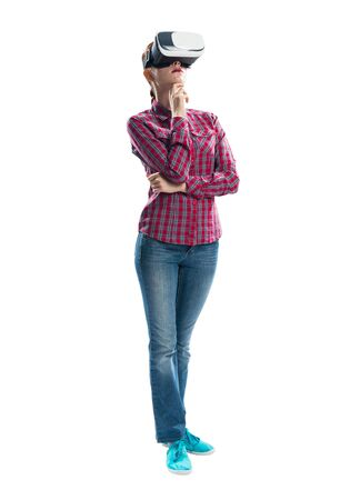 Young woman in checkered shirt and jeans wearing virtual helmet. Woman standing with folded hands. Cyber technology and new virtual reality. Studio photo by front view girl against gray background Banque d'images - 135430052