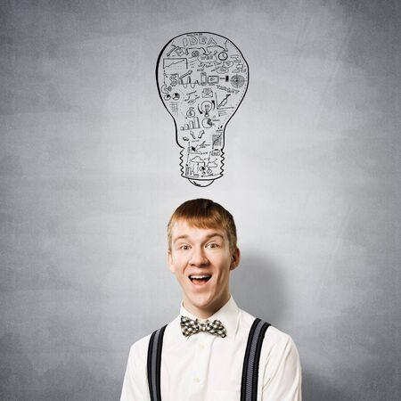 Gelukkige roodharige student met brede glimlach in eureka-moment. Creativiteit en probleemoplossend vermogen. Slimme jongen op de achtergrond van grijze muur met idee gloeilamp schets tekening overhead. Brainstormconcept Stockfoto