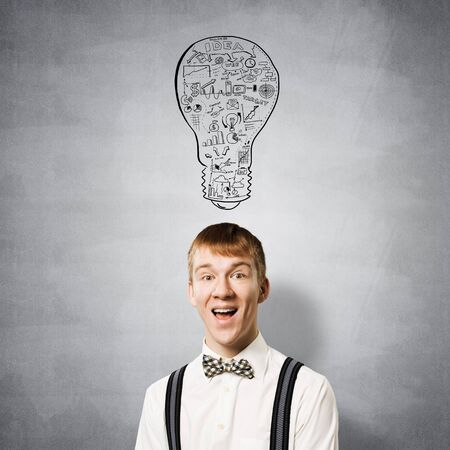 Happy redhead student with broad smile in eureka moment. Creativity and problem solving. Clever boy on background of grey wall with idea lightbulb sketch drawing overhead. Brainstorming concept Stock Photo