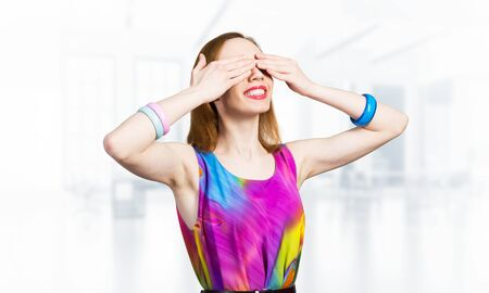 Redhead beautiful girl closing her eyes with hands. Charming lady wears bright dress and bracelets standing on blurred office interior background. Portrait of young woman waiting for pleasant surprise 스톡 콘텐츠