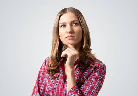 La femme aux cheveux bruns a l'air pensive vers le haut et essaie de se souvenir de quelque chose. Une fille perplexe a une expression faciale sérieuse. Portrait de belle femme porte une chemise à carreaux rouge sur fond gris.