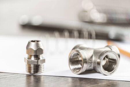 Raccordi e raccordi idraulici in acciaio per impianto idraulico. Pezzi di ricambio della conduttura idraulica che mettono sul tavolo. Nuove attrezzature per la riparazione o la costruzione di bagni. Assistenza tecnica idraulica professionale