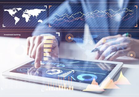 Stockbroker working with financial information at tablet computer. Interactive stock market tracking graph, trading indicators and exchange indexes. Global financial investment and trading concept