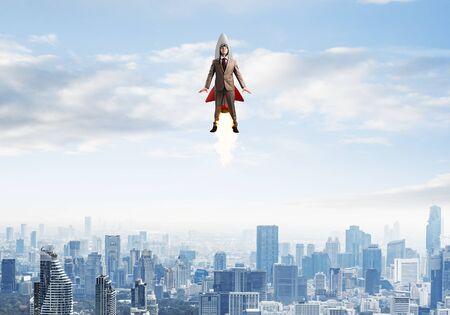 Uomo d'affari in tuta e cappello da aviatore che volano su un razzo. Uomo d'affari del supereroe che vola con il razzo jetpack nel cielo blu sopra il centro moderno. Avvio aziendale di successo. Concetto di crescita di carriera.