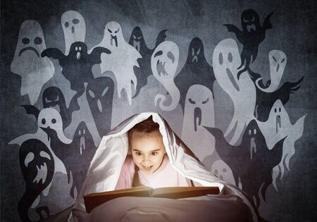 Engrossed little girl reading book in bed before going to sleep. Kid in pajamas with flashlight hiding under blanket. Fearful girl and imaginary monsters. Child reading fairy tales. Halloween holiday Reklamní fotografie