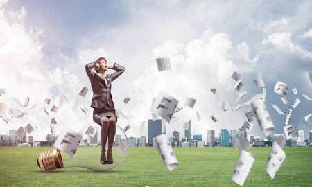Stressful woman sitting on big light bulb. Emotional screaming girl keeps hands on head. Businesswoman in despair on green meadow with falling paper documents. Business paperwork and accounting Reklamní fotografie - 135495322