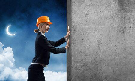 Schönheitsarchitekt, der Betonmauer drückt. Junger Spezialist für Schutzhelm auf Nachthimmelhintergrund. Ingenieur- und Entwicklungsunternehmen. Überwindung von Hindernissen und Lösung von Problemen.