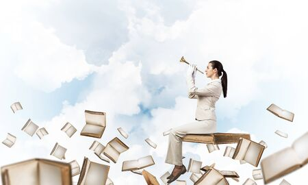 Attractive young woman playing trumpet on book. Businesswoman in white business suit sitting on floating in air book with music brass instrument in hands. University education, career and study.