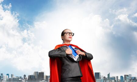 Serious business lady in red hero cape on blue sky and cityscape background. Portrait of business woman super heroine. Professional risk management. Brave super woman ready for new challenges.