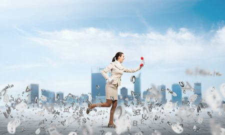 Woman running outdoor with red phone. Girl in white business suit with telephone on background modern cityscape. Hotline telemarketing and communication. Professional business assistance and support