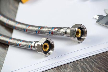Raccordi e collegamenti idraulici con segmenti di tubo intrecciato. Chiudere il sistema idraulico flessibile. Conduttura idraulica posa sul tavolo. Nuove attrezzature per la riparazione o il servizio di costruzione del bagno. Archivio Fotografico