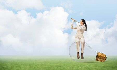 Woman sitting on big light bulb and playing trumpet brass. Young lady in white business suit and gloves with music instrument on green field. Business assistance and support concept with musician.