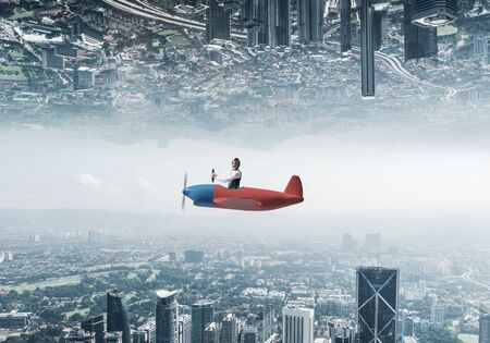 Aircraft pilot in leather helmet sitting in cabin of small airplane. Abstract image of two urban worlds located upside down to each other. Modern metropolis with high buildings and towers from glass.
