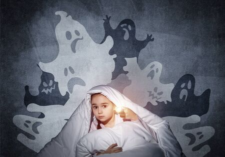 Scared girl with flashlight hiding under blanket. Frightened kid sitting in his bed at home. Night terrors of child. Beautiful girl in pajamas and boo ghosts silhouettes back on wall. Stock Photo