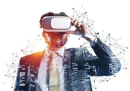 Handsome young man standing with VR headset. Businessman wearing VR goggles and exploring virtual reality. Caucasian businessperson in formal wear against white background. Enjoying new experience. Banco de Imagens