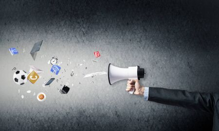 Businessman hand holding megaphone on wall background. Various things flying out from loudspeaker. Sport competitions announcement and advertisement. Business news broadcasting and online streaming Stock Photo