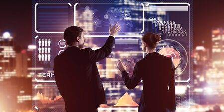 Two business people standing with back and working together with virtual screen Stock fotó