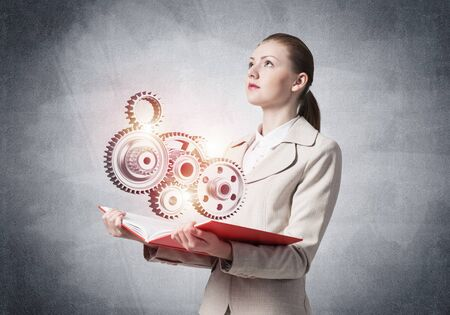 Woman showing abstract mechanism with cogwheels on open book. Construction and manufacturing. Mechanical technology machine engineering. Woman in white business suit on background of grey wall.