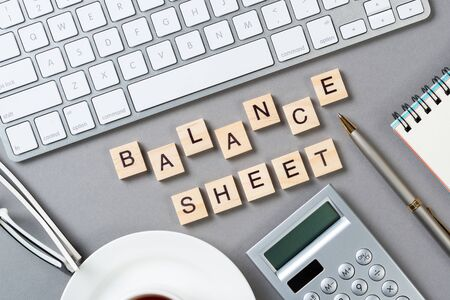 Balance sheet concept with letters on wooden cubes. Still life of office workplace with supplies. Flat lay grey surface with computer keyboard and calculator. Budget planning, audit and accounting.