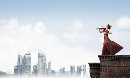 Young attractive girl playing violin at top of building. Mixed media