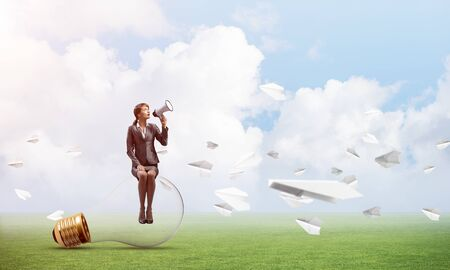 Young woman with megaphone sitting on lightbulb. Female speaker advertising new service or product on green meadow with flying paper planes. Businesslady shouting in loudspeaker. Business announcement