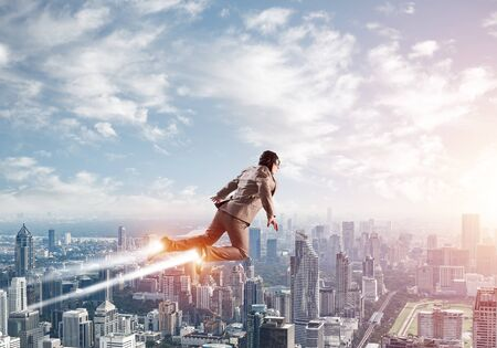 Businessman in suit and aviator hat flying in blue sky as superhero. Business person as superhero with jet flame above modern downtown. New challenges and winning. Career ambition and growth